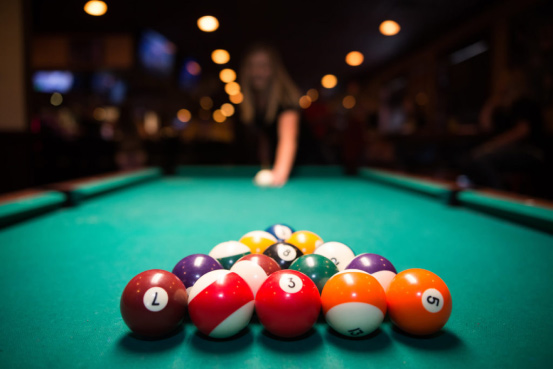 Close up of pool balls showing women out of focus shooting to break